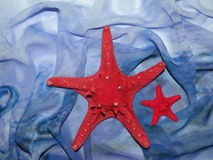 Red stars and blue fabric. Two red stars on blue rough fabric Stock Images