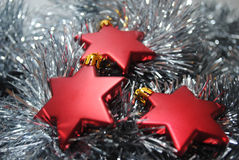 3 Red stars. Red Christmas stars laying in silver tinsel Stock Photos