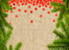 Red stars and christmas tree branch on linen texture Royalty Free Stock Image