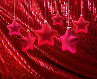 Red stars on red glitter canvas Stock Photo
