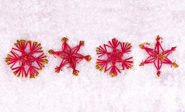 Red stars on snow. Four red and golden stars on snow Stock Images