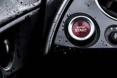 Red start button on a black wet car cockpit Royalty Free Stock Photo