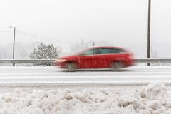 Red car, station wagon driving fast on the road in winter landscape, with snowy weather. Motion blur Royalty Free Stock Photography