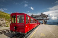 Red steam rack cogwheel train waiting in the Schafbergspitze station on the peak of Schafberg mountain peak in Austrian royalty free stock photography