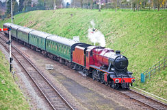 Red steam train. Large mainline steam train passing through a steep embankment with a full train of passengers Stock Images