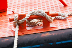 Red steel bollard with ropes mounted on deck Royalty Free Stock Photos