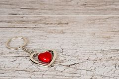 Red steel heart keyring on wooden table royalty free stock image