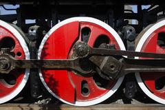 Red steel wheel and black crankshaft. The red steel wheel of the old gas engine and the black crankshaft, the detail feature Stock Photo