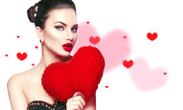 red steg Den sexiga unga brunettkvinnan med hjärta formade lilor kudde Arkivbild