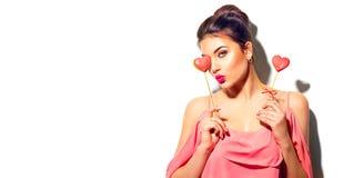 red steg För modemodellen för skönhet formade den glade unga flickan med Valentine Heart kakor i hennes händer royaltyfri bild