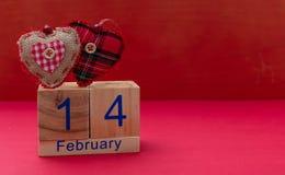 red steg 14 Februari och två röda tyghjärtor på röd bakgrund royaltyfri bild