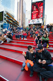 Red steps at TKTS Booth Times Square. Father and son sit on the sweeping cascade of 27 ruby-red structural glass steps of the TKTS Booth at 47th Street and Royalty Free Stock Images