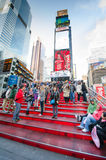 Red steps at TKTS Booth Times Square. Sweeping cascade of 27 ruby-red structural glass steps of the TKTS Booth at 47th Street and Broadway attracts tourists from Stock Photography