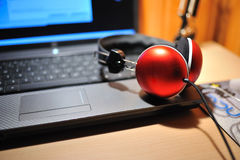 Red stereo headphones on notebook computer Stock Photos
