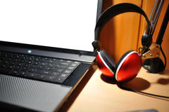 Red stereo headphones isolated besides laptop Royalty Free Stock Photography