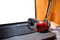 Red stereo headphones isolated on the notebook Royalty Free Stock Photography