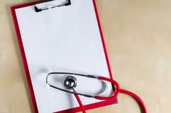 Red stethoscope on a red clipboard. Top view. Medical device. Treatment, health care. Heart examination. Studying the pulse. Doctor equipment hospital medicine royalty free stock image