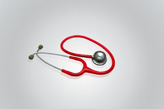 Red stethoscope in gray background. Medical instruments Stock Images