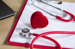 Red stethoscope and heart on a red clipboard. Near laptop. Medical device. Treatment, health care. Heart examination. Studying the. Pulse. Close-up doctor stock photos