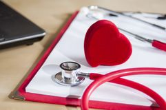 Red stethoscope and heart on a red clipboard. Near laptop. Medical devices. Treatment, health care. Heart examination. Studying. The pulse. Close-up doctor stock image
