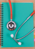 Red stethoscope lying on a thin green book. Royalty Free Stock Photo