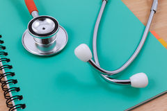 Red stethoscope lying on a thin green book. Stock Photo