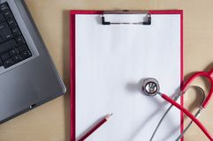 Red stethoscope and red pencil on a red clipboard. Near laptop. Medical device. Top view. Treatment, health care. Heart. Examination. Studying the pulse doctor stock photography