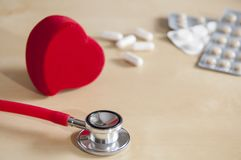 Red stethoscope and red heart on a table. Near tablets and capsules. Medical device. Treatment, health care. Heart examination. Studying the pulse doctor stock images