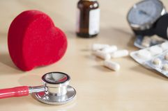 Red stethoscope and red heart on a table. Near tablets, capsules, medicine bottle and tonometer. Medical device. Treatment, health. Care. Heart examination royalty free stock photo