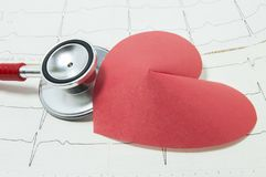 Red stethoscope and shape of red paper heart lie side by side on lines of printed ECG, symbolizing heart beat. Concept for diagnos. Is and treatment of heart stock image