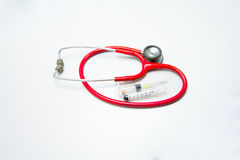Red stethoscope and syringes. In gray background Royalty Free Stock Photos