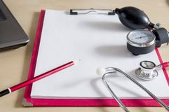 Red stethoscope, tonometer and red pencil on a red clipboard. Near laptop. Medical device. Treatment, health care. Heart. Examination. Studying the pulse doctor stock photo
