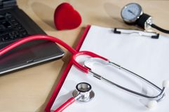 Red stethoscope, tonometer on a red clipboard. Near laptop and heart. Medical device. Treatment, health care. Heart examination. Studying the pulse doctor stock photo