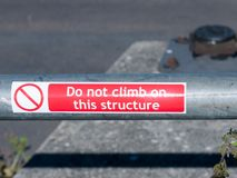 Red sticker on metal rail do not climb on this structure Royalty Free Stock Photography
