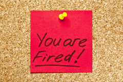 Red sticky note 'You are Fired!'. Red sticky note on an office cork bulletin board with 'You are Fired!' on it Stock Photos