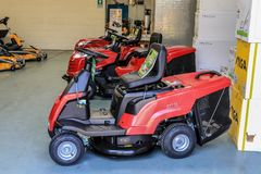 A row of red sit on lawn mowers. Red stiga sit on lawn mowers for cutting lawn grass  Doing chores and home maintenance in show room Stock Image