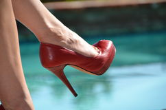 Red Stiletto shoe on woman's foot. Red high heel shoes against pool in summer sunshine Los Angeles royalty free stock image