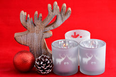 Red still life background with grey, white wooden reindeer Christmas decoration Stock Image