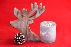 Red still life background with grey, white wooden reindeer Christmas decoration Stock Photo