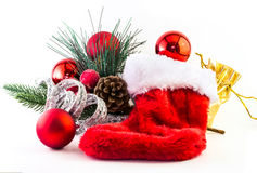 Red stocking with decorations. Red stocking with decorations, pine leaves, and cones, golden bag Stock Photo