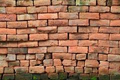 Red stone brick wall with moss. Irregular shapes of red stone brick wall background Royalty Free Stock Photos