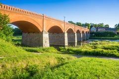 Red stone bridge in Latvia, Kuldiga in summer sunny evening royalty free stock images