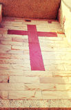 Red stone cross of christ built into brick wall, vintage style. Royalty Free Stock Image