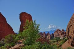 Red stone desert scene with towering rock and mountains. Arches National Park Utah desert landscape with towering rock formations, green shrubs, and mountains Stock Photo