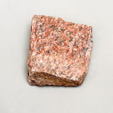 Red stone. Red granite stone on bright grey surface Stock Images