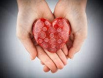 Red stone heart in young woman hands, vignette toned Stock Photography