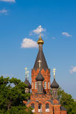 Red stone orthodox church. With black and golden domes against the backdrop of an overcast sky, close-up Royalty Free Stock Photography