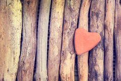 Red stone in the shape of a heart on wood background Royalty Free Stock Photography