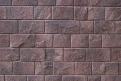 Red stone wall background, Large stone-clad facade brown color. Textured red stone wall background, Large stone-clad facade brown color royalty free stock photography