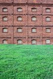 Red stone wall. Red stone brick wall. Background. Lawn Royalty Free Stock Image